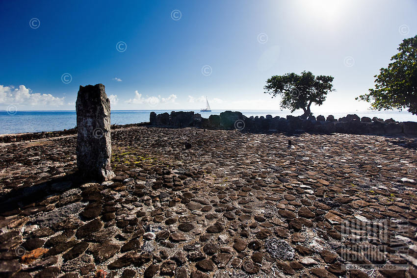 Modern sailing catamaran sails past altar stone and ancient temple Taputapuatea Marae on Raiatea, French Polynesia