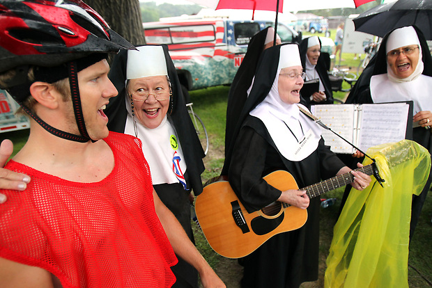 "Rider Jonathan Stichter, left, of Sigourney joins with the Singing Nuns from St. Athanasius Church of Jesup Friday in Gilbertville.  They were singing a rousing rendition of ""A Bicycle Built for Two."""