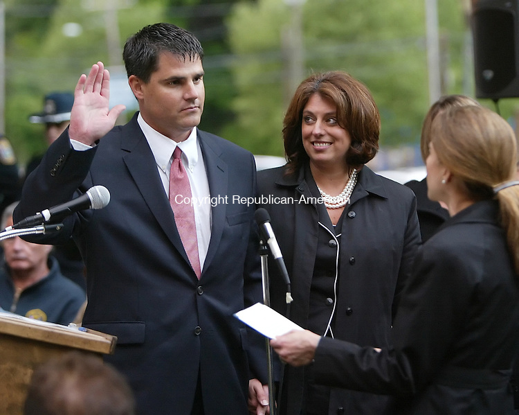 NAUGATUCK, CT 05/18/09- 051809BZ01- With his wife Eileen by his side, Naugatuck Mayor Bob Mezzo (D) takes the oath of office from Secretary of State Susan Bysiewicz during a ceremony on the green in Naugatuck Monday night.<br /> Jamison C. Bazinet Republican-American