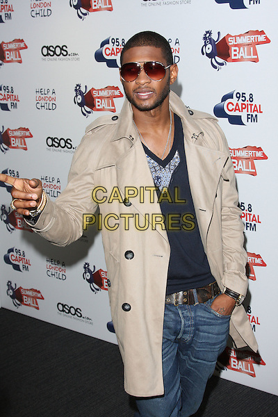USHER (Usher Raymond).Capital FM Summertime Ball at Wembley Stadium, London, England, UK, June 6th 2010..half length beige trench coat hand gesture jeans sunglasses black top finger pointing .CAP/ROS.©Steve Ross/Capital Pictures.