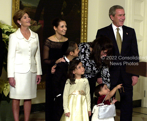 Ahuva Felzenberg (little girl at lower right center) points to the Chanukah Menorah as United States President George W. Bush looks on.  For the past three years, the President has participated in a Menorah lighting before the annual White House Hanukkah Reception.&nbsp;Her father, Captain Shmuel Felzenberg, is serving in Iraq as the senior Jewish chaplain with the United States Army's 84th Engineer Battalion, from Schofield Barracks, Hawaii. Captain Felzenberg is scheduled to return home in January.  The four-foot-tall sterling silver Menorah is on loan from the Boca Raton Synagogue in Boca Raton, Florida. The Menorah was made in Israel and purchased for the synagogue by two congregants, Nachman and Jamie Feig.&nbsp;Because tonight is the third night of Chanukah, the lighters will light three candles and the shamash, the main candle. From left to right: First lady Laura Bush; Hadassah Teitelbaum, sister of Captain Felzenberg, Dovid, Freida, and Ahuva Felzenverg; and President Bush.<br /> Credit: Ron Sachs / Pool via CNP