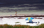 young child runs along ocean toward his blue pail on Loggehead Beach, Bahia Honda State Park, Florida Keys.  A blue & green cahir & beach umbrella sit on beach in foreground