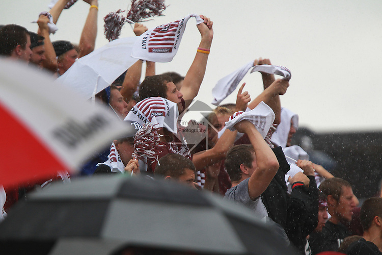 Lindenwood-Belleville student fans wave rally towels which were handed out at the entrance to the stadium.  The towels were made up for the inaugural football game.  Here, they wave the towels and yell for the team at the start of the second quarter, when a brief downpour hit the stadium, during the first football game in Lindenwood-Belleville history.