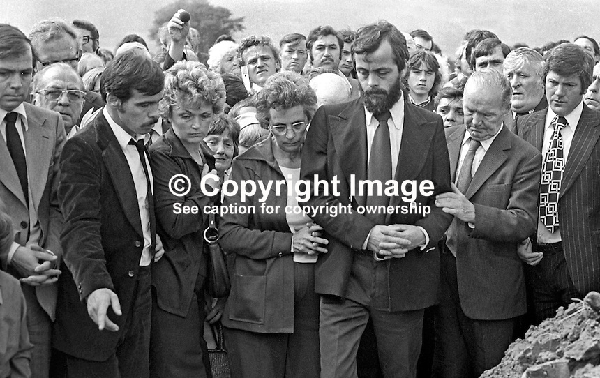 Jackie Maguire, with beard, at the grave of his three children, Joanne, 8 years, John, 2 years, and Andrew, 6 weeks, who died as a result of one of the most tragic and horrific incidents of the N Ireland Troubles on 10th August 1976. His wife, Anne, was unable to attend her childrens' funeral as she was still seriously ill in hospital. A car driven by Daniel Lennon, aka Danny Lennon, member, Provisional IRA,  mounted the pavement and ploughed into the Maguire family. Lennon died at the wheel having been shot by British soldiers in hot pursuit. The incident gave rise to the birth of the Peace People organisation led by Mairead Corrigan, aunt of the dead children, and a local woman,Betty Williams. 197608130371f .<br />