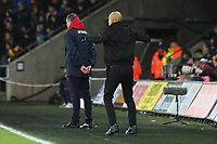 Manchester City manager Pep Guardiola celebrates his sides second goal of the match as Swansea City manager Paul Clement watches on during the Premier League match between Swansea City and Manchester City at the Liberty Stadium, Swansea, Wales, UK. Wednesday 13 December 2017