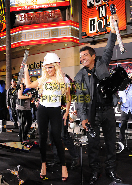 BRIDGET MARQUARDT & GEORGE LOPEZ.The Hard Rock Cafe Hollywood's grand opening party in Hollywood, California, USA..October 21st, 2010.full length white t-shirt black trousers  hard hat guitar broken arms in air destroyed goggles scarf.CAP/RKE/DVS.©DVS/RockinExposures/Capital Pictures.