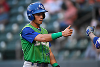 Left fielder Marten Gasparini (24) of the Lexington Legends is greeted after scoring a run in a game against the Greenville Drive on Friday, June 30, 2017, at Fluor Field at the West End in Greenville, South Carolina. Lexington won, 17-7. (Tom Priddy/Four Seam Images)