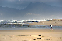 Woman running in the morning by Flamingo lake estuary near Hermanus, South Western Cape, South Africa