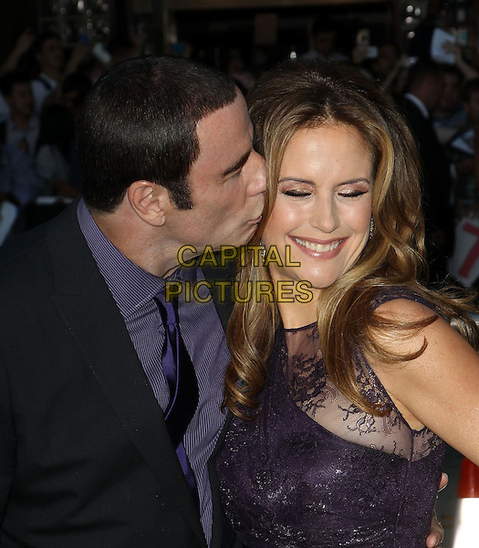 John Travolta and Kelly Preston.The World Premiere of 'Savages' held at The Grauman's Chinese Theatre in Hollywood, California, USA..June 25th, 2012.half length suit dress married husband wife lace purple black headshot portrait profile kiss kissing smiling .CAP/ADM/KB.©Kevan Brooks/AdMedia/Capital Pictures.