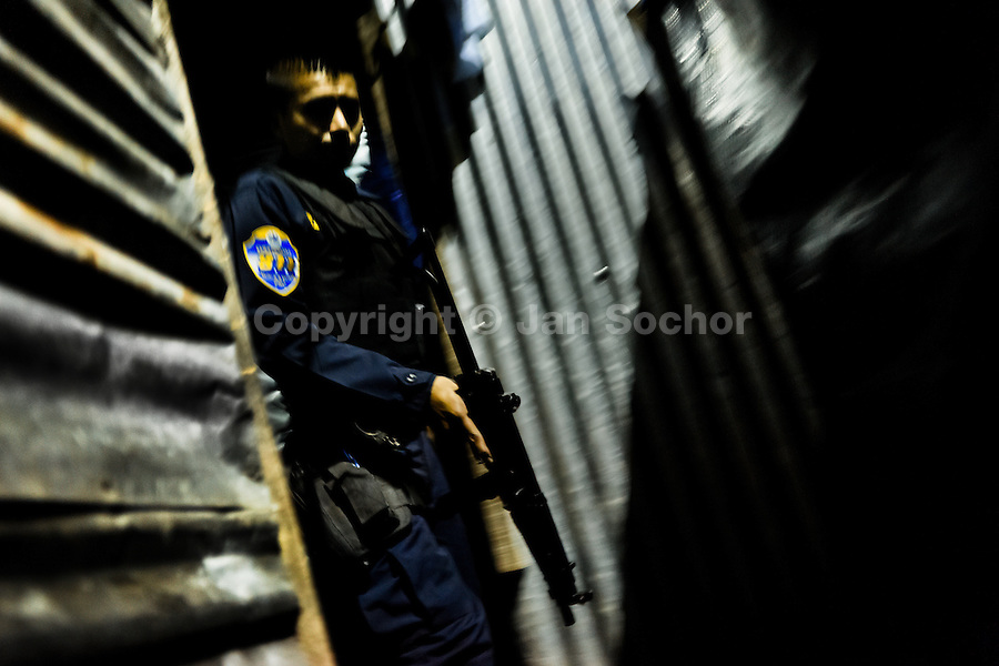 A policeman from the special emergency unit (Halcones) chases supposed gang members during the night in a gang neighbourhood of San Salvador, El Salvador, 15 December 2013. Although the murder rate in the country has dropped significantly, after a truce between two major street gangs (Mara Salvatrucha and Barrio 18) was agreed in 2012, the lack of security and violence are still the main issues in people's daily life. Due to the fact the gangs have never stopped their criminal activities (extortions, distribution of drugs and kidnappings), the Police anti-gang forces keep running their operations and chasing the 'homeboys' (how the gang's foot soldiers usually call themselves) in the poor, socially deprived suburbs of Salvadoran cities.