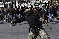 Pictured: A man throws a brick towards riot police officers Friday 12 February 2016<br /> Re: Violent clashes between farmers and riot police outside the Ministry of Agricultural Development in Athens, Greece. The farmers travelled from Crete to protest against pension and welfrae reforms proposed by the Greek government,