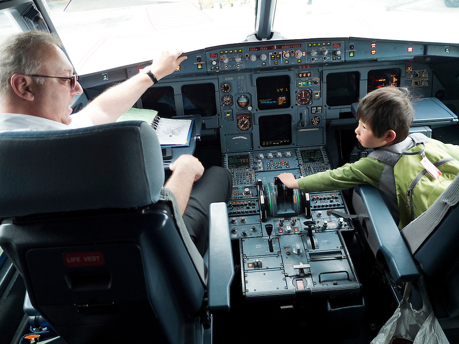 A friendly pilot welcomes Holden Miller, 4, into the cockpit of a Delta Airlines flight that landed at the Bradley International Airport in Hartford, Conn., on May 10, 2012. The photo was made during travel to Northampton, Mass., for the May 12, 2012 wedding of Hannah Kurtis and Erik Tejero.