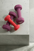 A group of gym weights on the grey marble floor of a bathroom