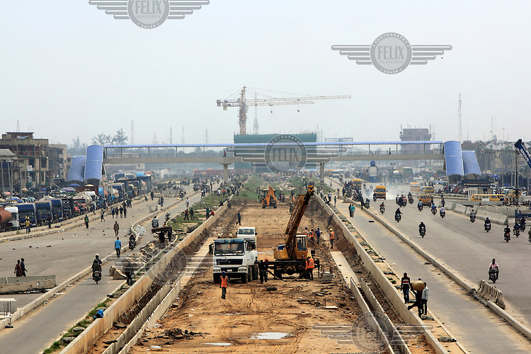 Construction work, taking place among the busy Lagos traffic, on the Orile light rail terminal. This is part of a private/public enterprise to build a mass transit system in the city.