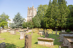 Tower of church of Saint Mary, Berkeley, Gloucestershire, England, UK gravestones and chest tombs in graveyard