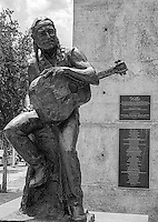 Willie Nelson statue in black and White in downtown austin.  Part of the art in public places. This statue of Willie is outside of the ACL club and they dedicated the street corner to him.