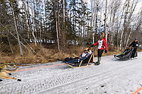 Xxxx Xxxx and team run past spectators on the bike/ski trail with an Iditarider in the basket during the Anchorage, Alaska ceremonial start of the 2015 Iditarod race. Photo by Ed Bennett/IditarodPhotos.com