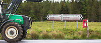 Farm tractor passing postbox and Gaelic language signpost Salen and Kilchoan on a B road in Highlands of Scotland