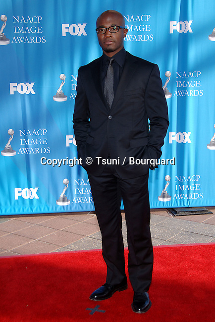 Taye Diggs  at the NAACP Image Awards at the Shrine Auditorium In Los Angeles.<br /> <br /> full length<br /> eye contact<br /> glass