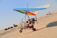 Microlite plane with two passengers landing in Sahara desert, Tunisia, Douz