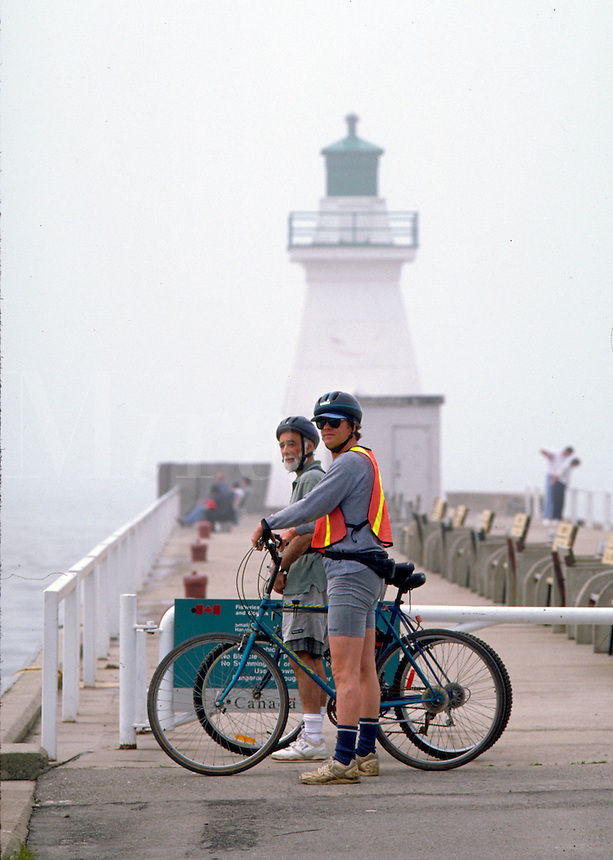 Two bicyclists looking out over Lake Erie from a dock at Port Dover. Port Dover Lighthouse is in the background. Bicyclists. Port Dover, Canada Ontario.
