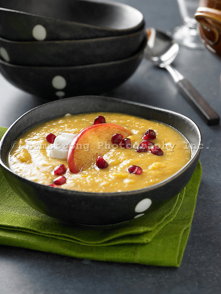 A bowl of squash soup garnished with apple slice, pomegranate, and sour cream