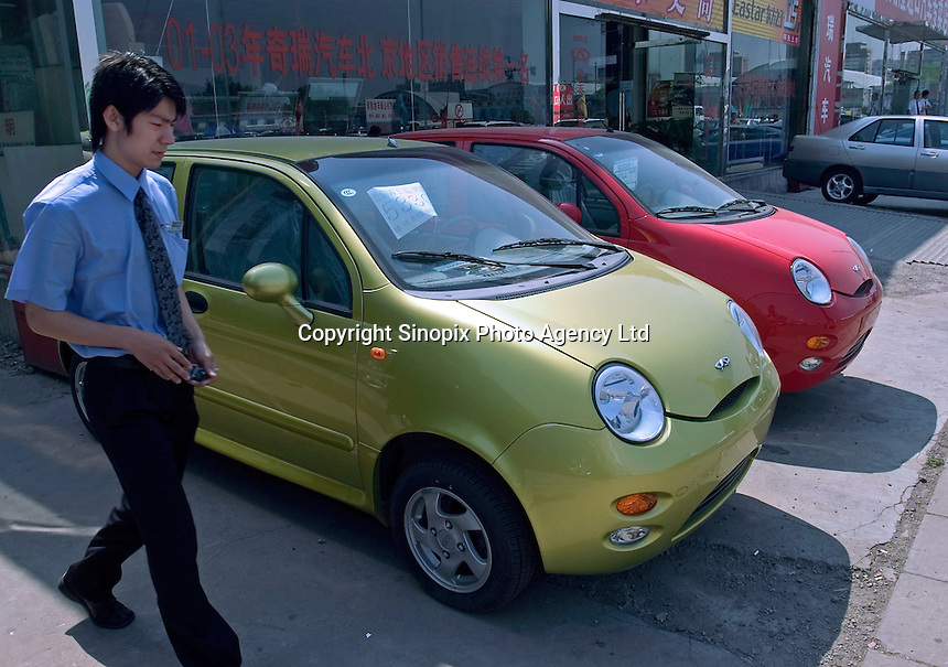 A man walks past Chery QQ at a Chery showroom in Beijing, China..