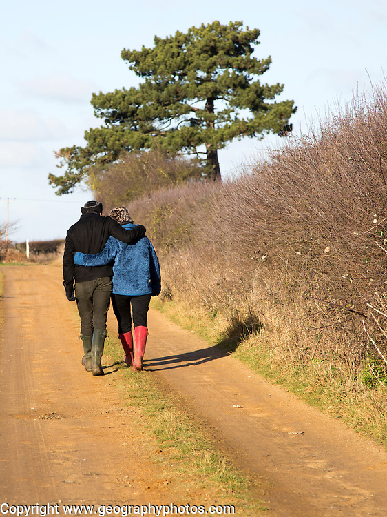 Young couple man woman winter country walk from behind, Suffolk, England, UK