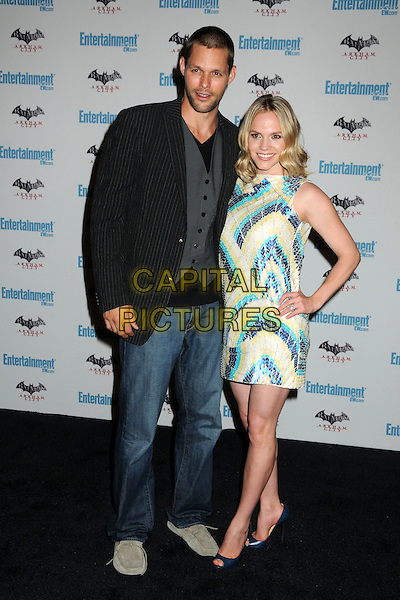 Justin Bruening and Alexa Havins.5th Annual Entertainment Weekly Comic-Con Party held at The Hard Rock Cafe, San Diego, California, USA..July 23rd, 2011.full length jacket jeans denim white green yellow print dress hand on hip black stubble smiling  facial hair married husband wife.CAP/ADM/BP.©Byron Purvis/AdMedia/Capital Pictures.
