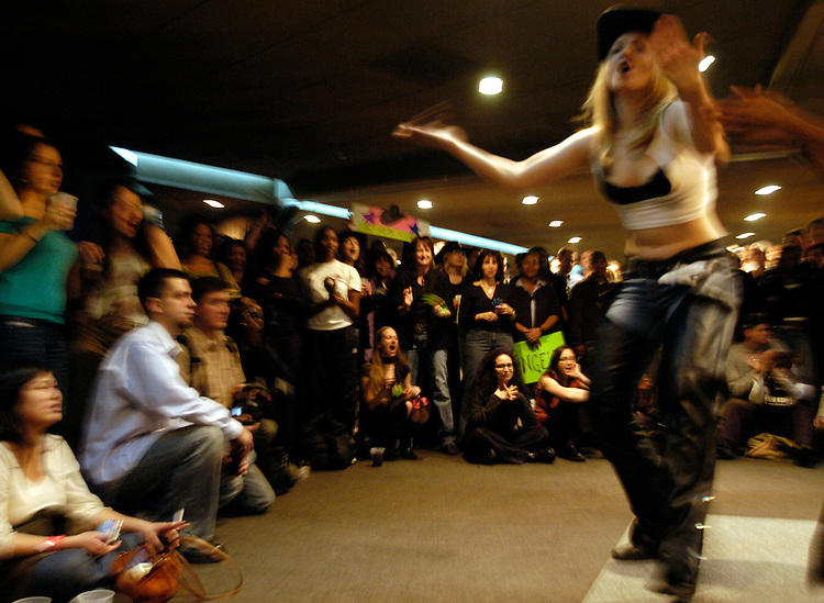 """A crowd watches contestants perform at the """"Coyote Ugly Bartender Search Finals"""" for the new Washington, DC bar location at the F Street bar in the MCI Center. More than 75 women were judged on their dancing, drink-mixing, and """"entertainment"""" abilites. The new bar, based on the eponymous movie, where women bartenders yell at crowds and dance on the bar, will open downtown on Febuary 13th, 2004."""
