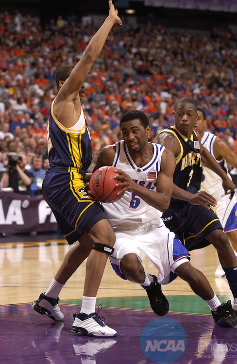 5 April 2003: Kansas guard Keith Langford (5) drives to the basket past Marquette guard Dwaye Wade (3) and guard Joe Chapman (32) during the Division I Men's Final Four semifinal game held in the Louisiana Superdome in New Orleans, LA. Kansas went on to defeat Marquette 94-61 to advance to the championship game. Photo by Ryan McKee/NCAA Photos