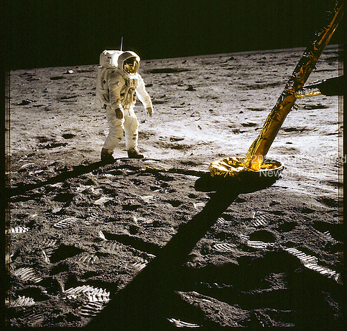 The Moon - (FILE) -- Apollo 11 astronaut Edwin Aldrin stands near the leg of the lunar module on the Moon. Despite the fact that the backpacks and astronauts only weighed 1/6 on their 350 pound Earth weight, their center of gravity was shifted so they had to lean slightly forward to balance. Footprints are clearly visible in the foreground..Credit: NASA via CNP