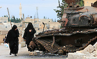 Photographer: Rick Findler..06.10.12 Women walk past a destroyed tank lying at the side of a road in the Syrian town of Azaz. The town was destroyed by helicopter gunships and fighterjets belonging to President Assad.