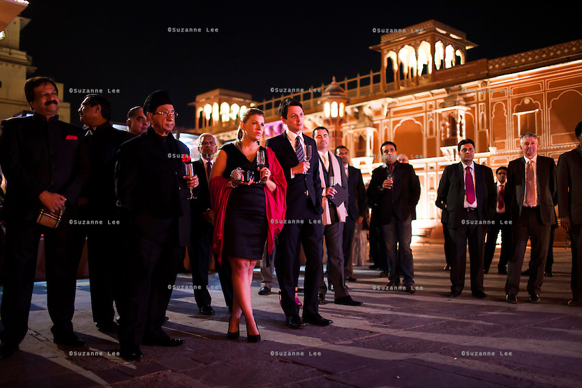 Guests sip pink champagne in front of a jewelry exhibition while listening to a speech before a violin recital at the OzFest Gala Dinner in the Jaipur City Palace, in Rajasthan, India on 10 January 2013. Photo by Suzanne Lee