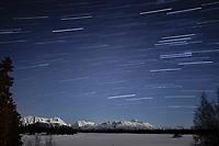 Stars streak in the night sky over the Alaska Range and Finger Lake at Winter Lake Lodge in Southcentral, Alaska