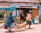 PERU, South America, Latin America, shepherd carrying dead sheep with shop in the background