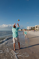 Family plays on beach along Gulf of Mexico in Naples, Florida, USA. Photo by Debi PIttman Wilkey
