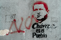 A spray paint stencil artwork, depicting Venezuelan president Hugo Chavez and saying 'Chavez is the People', is seen painted in the street of Caracas, Venezuela, 19 February 2006.