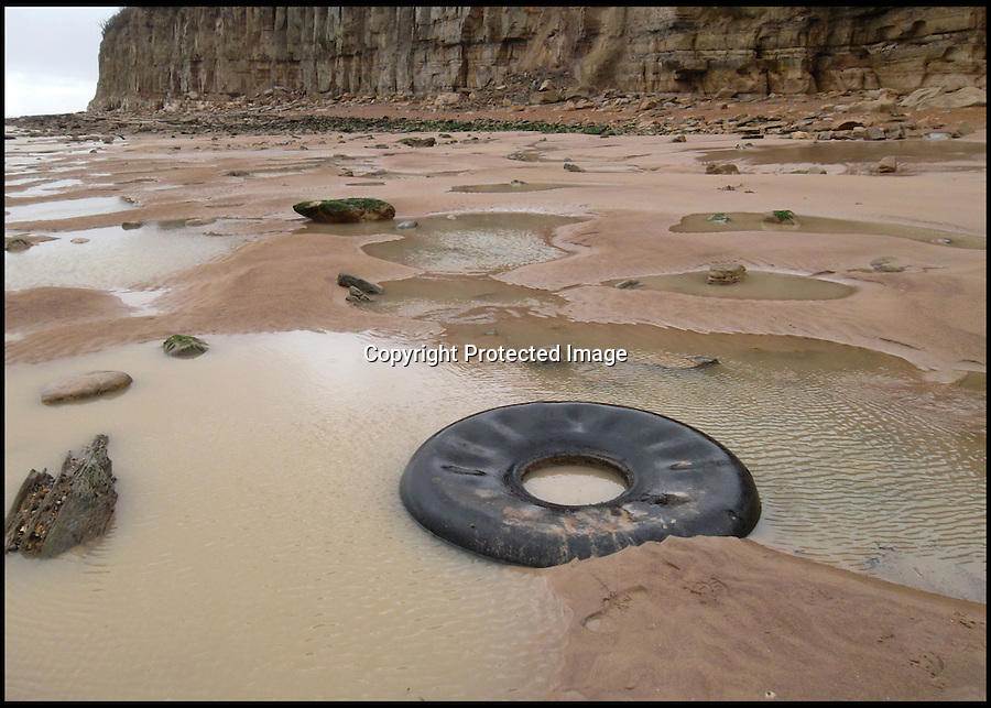 BNPS.co.uk (01202 558833)<br /> Pic: AndySaunders/BNPS<br /> <br /> ****Please use full byline****<br /> <br /> A huge tyre from a downed wartime bomber has been exposed on south coast beach Fairlight, near Hastings, East Sussex after the recent winter storms.<br /> <br /> The black rubber tyre was buried in the sand 60 yards from the shore after a Wellington bomber it was attached to crash-landed there 74 years ago.<br /> <br /> The aircraft broke up on landing in the sea, although the main fuselage was later recovered. Incredibly, all six members of the crew survived the crash.&nbsp;<br /> <br /> The recent strong winds and high tides are believed to have swept much of the sand away, leaving the tyre exposed at low tide.