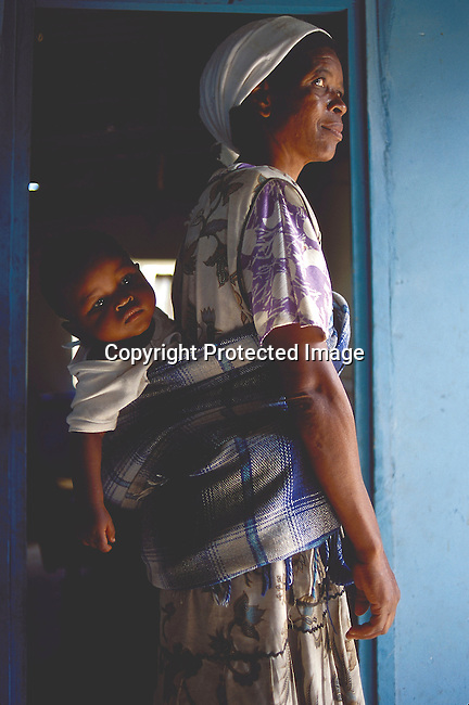 SIAIDSG20204.Social Issues. AIDS. Natal. Relative of a AIDS patient, she is standing with  a baby on her back. 3/99. .©Per-Anders Pettersson/iAfrika Photos