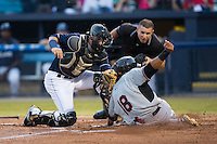 Luke Tendler (18) of the Hickory Crawdads is tagged out at home plate by Asheville Tourists catcher Dom Nunez (9) as home plate umpire Jonathan Parra looks on during Game Three of the South Atlantic League Championship at McCormick Field on September 17, 2015 in Asheville, North Carolina.  The Crawdads defeated the Tourists 5-1 to win the 2015 South Atlantic League Championship.  (Brian Westerholt/Four Seam Images)