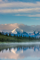 Early morning sunrise on the face of Mt Brooks and Wonder Lake, at the west end of Denali National Park, Interior, Alaska.