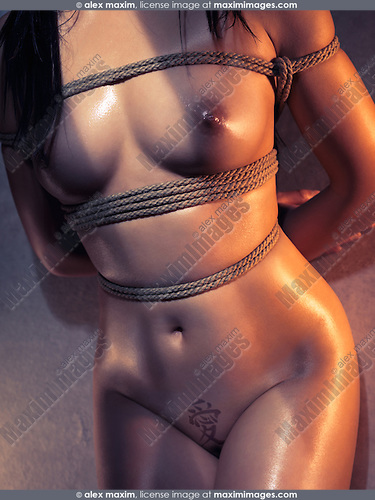 Beautiful naked asian woman body tied with Japanese Shibari rope bondage and Kanji character Ai, meaning Love, tattoo. Art nude photo.