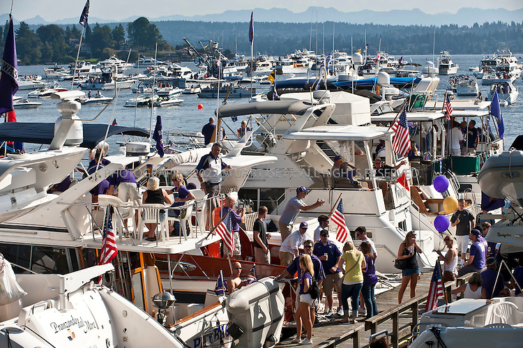 9/24/2011--Seattle, WA, USA...Boast mored up along HUsky Harbor enjoy a morning of tailgating before a UW football game...The 'Big Dawg', owned by Lisa and Tim Kittilsby, is the biggest, most prominent boat that attends regular boat tailgate parties on docks near the UW (University of Washington) Husky Stadium. Up to 500 boats will tie up outside Husky Stadium on football game days, ranging from from small boats to huge yachts. The Big Dawg is a 92-foot, two-story yacht that dominates the tailgate parties...The tradition started when Lisa and Tim Kittilsby's parents, Frank and Jeanie Miles, took a 23-foot boat called The Mixer to a game over 40 years ago...©2011 Stuart Isett. All rights reserved.