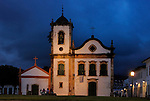A group of four senior tourists enjoying the nighfall at Paraty's oldest church, the Nossa Senhora dos Pardos Libertos (built 1722); Paraty, Espirito Santo, Brazil. The beautiful colonial town of Paraty has been a UNESCO World Heritage Site since 1958. --- No signed releases available.