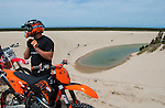 KTM Dirt bike rider fastens helmet strap on the Oregon Dunes with sand lake, ATV riders and the Pacific Ocean in the background