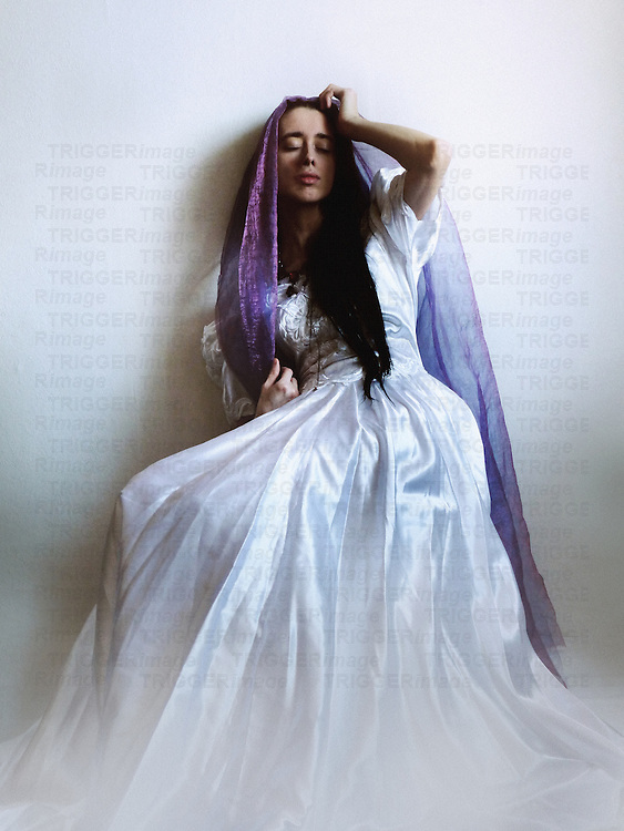 A woman in a vintage white gown and a violet veil, with long black hairand closed eyes, seated in front of a wall in a lazy manner.