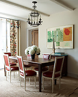 The chairs and 19th-century farm table in the breakfast room are French, the tole lantern is 18th-century, the print is by Robert Rauschenberg, and the curtains are faced with 19th-century crewelwork panels.