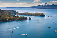 Commercial fishing vessels, Cape purse seiners position themselves in Sitka Sound, on the north side of Middle Island, for the first Herring Sac Roe fishery opener in 2006, southeast, Alaska. Inactive volcano, Mount Edgecumbe in the distance.