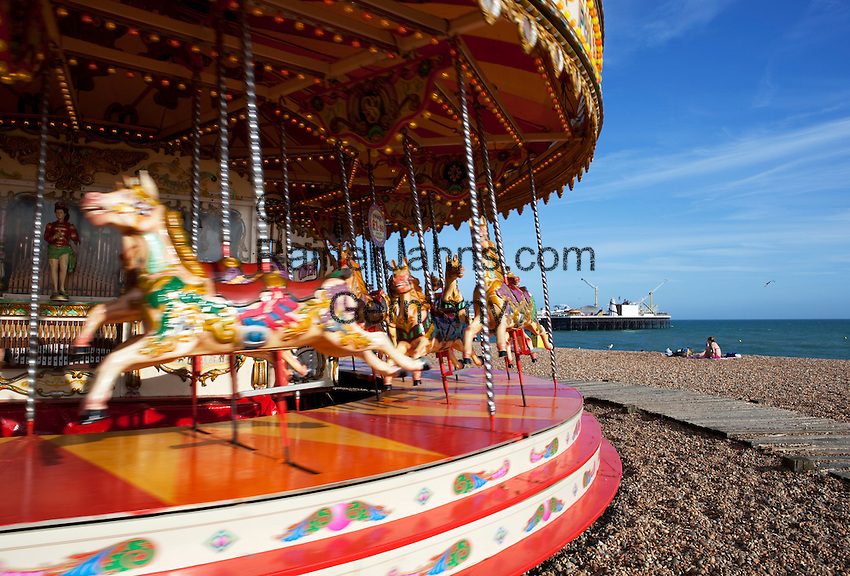 Great Britain, England, East Sussex, Brighton: Carousel on Brighton beach with Brighton Pier behind